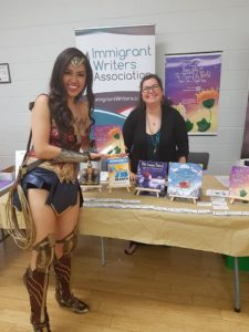 A young lady dressed as Wonder Woman presents a book at Andreea's booth
